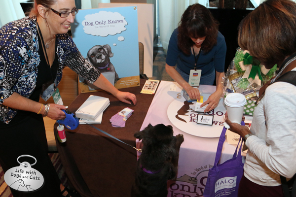 Belle, author of Dog Only Knows checks in at her booth.