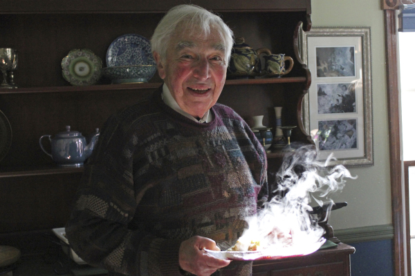 My dad with a warm breakfast, lit by a sunbeam, Thanksgiving 2011