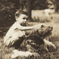 Sepia photo with young boy and Airedale dog